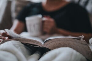 person reading book in bed with coffee
