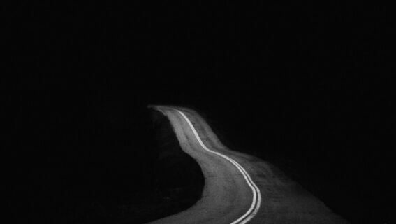 spooky picture of empty road leading into darkness